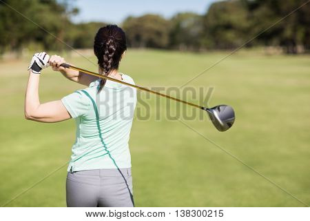 Rear view of golfer woman taking shot while standing at golf course
