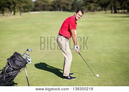 Full length portrait of man playing golf while standing on field