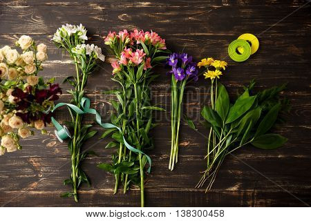 Bright colorful irises, herberas, leaves and  alstroemerias on wood table, roses in vase. From above.