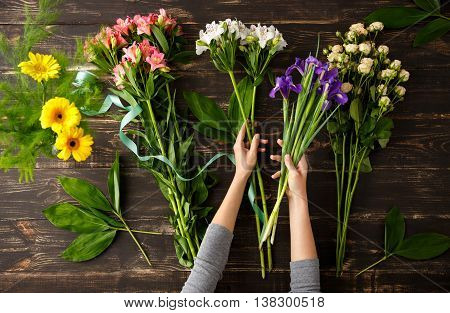 Bright colorful alstroemerias and irises in hands, roses on wood table, herberas in vase. From above.
