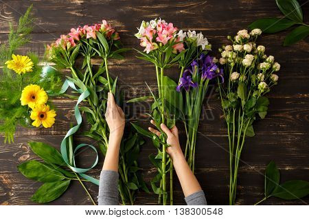 Bright colorful alstroemerias in hands, irises and roses on wood table, herberas in vase. From above.