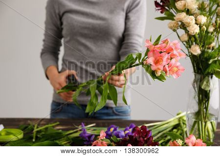 Girl in gray blouse and jeans make a bouquet over gray background, cutting alstroemeria stem, roses in vase, flowers and vase on wood table.