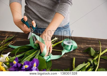 Girl in gray blouse and jeans make bouquet over gray background, cutting green ribbon, flowers on wood table.