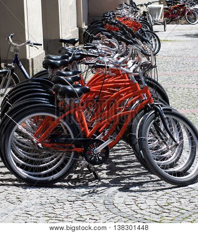 Arrangement of Parked Rental Bicycles on Paving Stone Sidewalk in Summer Day in Europe Outdoors