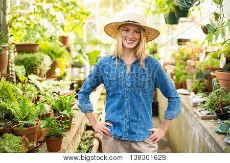 Portrait of confident female gardener at greenhouse