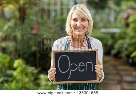 Portrait of mature woman holding open sign placard at greenhouse