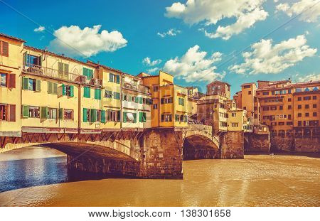 Vintage looking bridge with houses ponte vecchio in florence old town on arno river famous touristic place italy