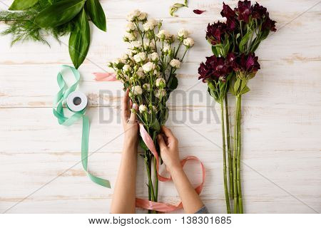 Bright colorful alstroemerias, roses with pink ribbon in hands on wood table. From above.