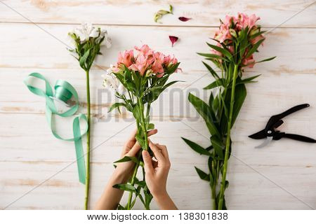 Bright colorful alstroemerias in hands, green ribbon on wood table. From above.
