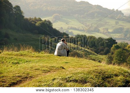 Tourist sit on peak of hill and watching into colorful valley. Sad man. Man sit. Fall mountain mist. Sad tourist sit in mist.