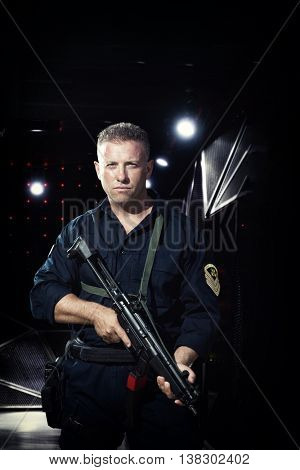 Man in military outfit holding a  machine gun