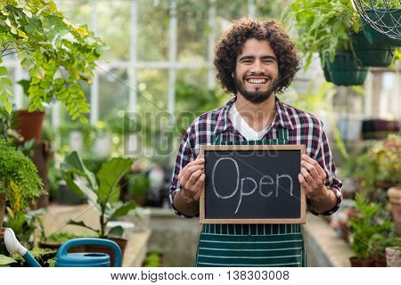 Portrait of happy bearded gardener holding open sign placard at greenhouse