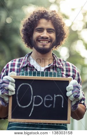 Portrait of smiling male gardener holding open sign placard