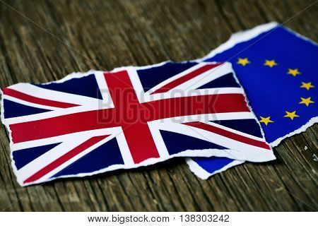 the flag of the European Community and the flag of the United Kingdom put together on a rustic wooden surface