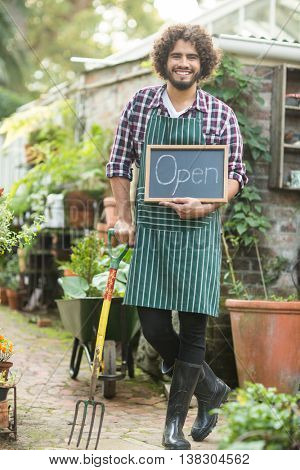 Portrait of male gardener with open sign holding gardening fork outside greenhouse