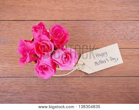 Top view of pink rose flower in the basket and handwriting Happy Mother's Day on brown label paper with dark wood background