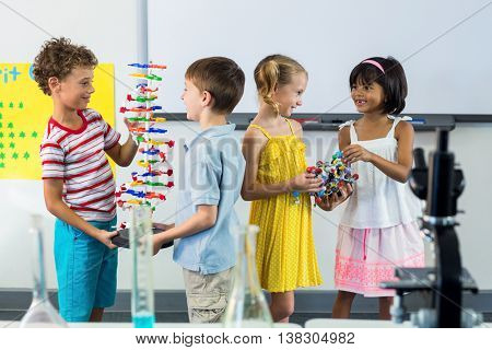 Happy schoolchildren with scientific equipment in laboratory