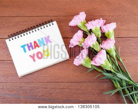Bouquet of sweet pink Carnation flower and word spell Thank you on notebook with dark wood background on top view