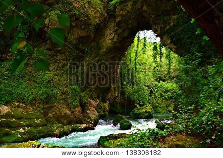 Gods Bridge. Unique cave with greenery and river.