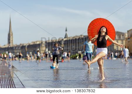 Asian woman holding an umbrella, dancing and splashing the water mirror in place de la bourse at Bordeaux, France
