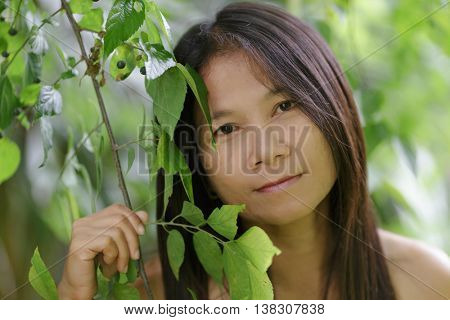 Asian woman soft outdoor portrait among tree leaves