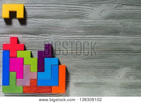 The concept of logical thinking. Geometric shapes on a wooden background. Tetris toy wooden blocks, flat lay