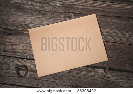 Paper sheet on old wooden background, top view