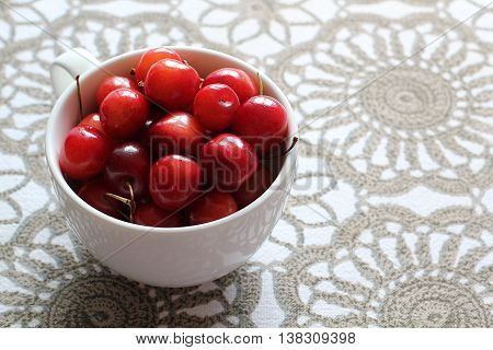 Cherries in white cup on desk. Stock photo.