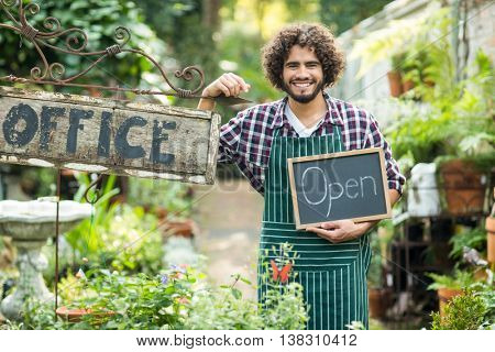 Male gardener holding open sign while standing by office placard outside greenhouse