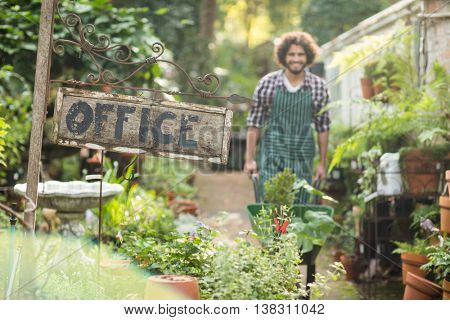 Office placard by plants while male gardener working in background at greenhouse