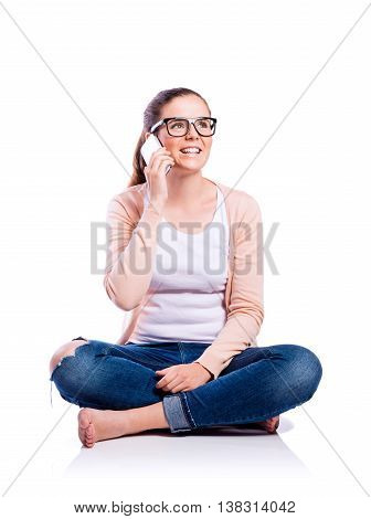 Teenage girl in white t-shirt, pink cardigan, jeans and trendy black eyeglasses, holding a smart phone, making a phone call, sitting on the floor, young beautiful woman, studio shot on white background, isolated