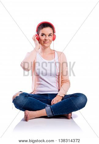 Teenage girl in white t-shirt, pink cardigan and jeans, sitting on the floor, earphones on head, listening music, young beautiful woman, studio shot on white background, isolated