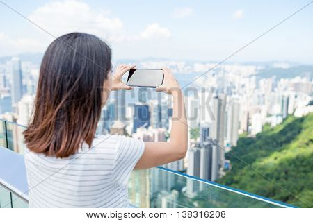 Woman taking photo with mobile phone in the peak of Hong Kong
