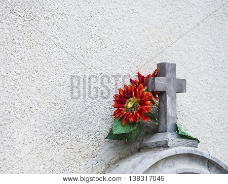Stone cross with a flower near a wall.