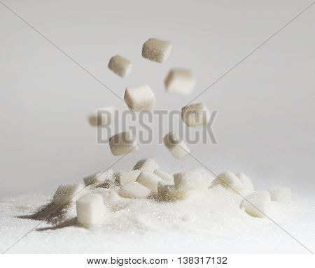 Sugar cube is falling down on a pile of sugar.