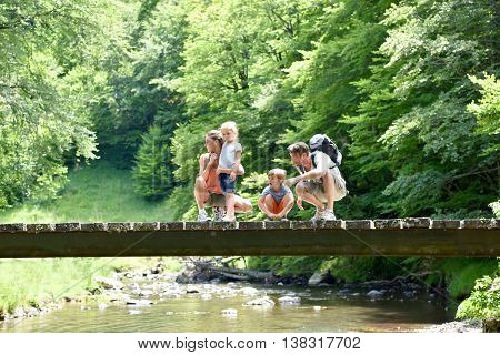 Family of four walking on a bridge crossing the river
