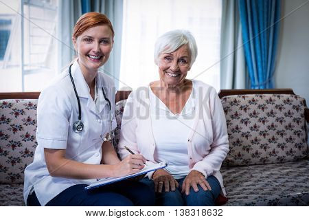 Smiling doctor consulting with senior woman at home