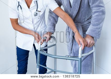 Mid-section of female doctor helping senior man to walk with walker in hospital