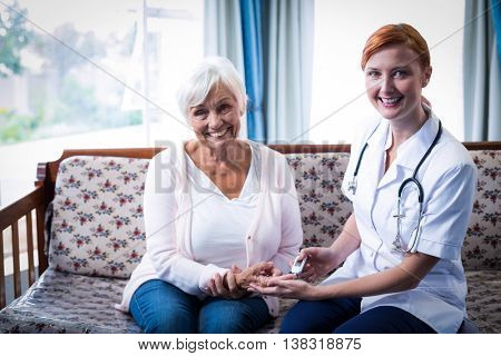 Smiling doctor testing a patients glucose level using a digital glucometer