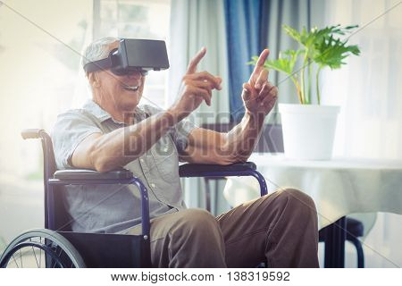 Happy senior man on wheelchair using VR headset at home