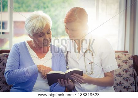 Doctor and patient reading a book at home