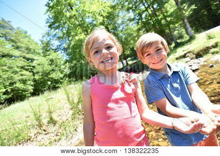 Happy litle kids in river fishing tadpoles