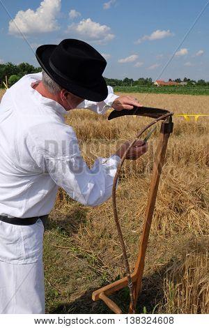 NEDELISCE, CROATIA - JULY 02, 2016: Farmer sharpening the scythe in the field in wheat fields in Nedelisce, Croatia on July 02, 2016
