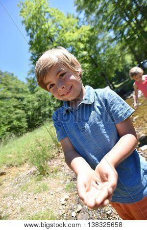 Happy little boy catching tadpoles in river