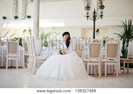 Temptation Model Brunette Bride At Exciting Wedding Dress Sitting On Chair At Wedding Hall