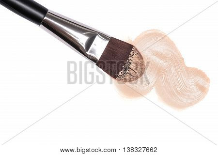 Close-up of flat makeup brush with sample of liquid foundation light shade on white background
