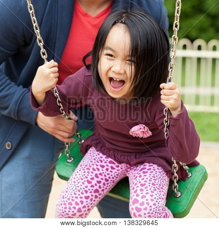 Father spends time with his cute daughter on the playground
