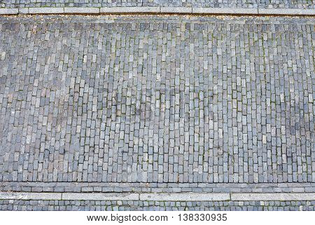 Cobblestone street and pavement seen from above.