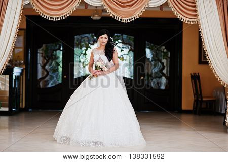 Temptation Model Brunette Bride At Exciting Wedding Dress With Bouquet At Hands At Hall
