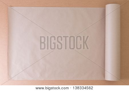 Opened roll of plain brown paper on cardboard for creative artistic designs or craft work overhead view with copy space